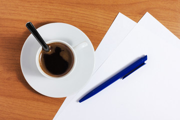 Cup of coffee on table with papers and pen