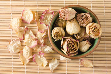 Dried rosebuds in teacup and petals top view