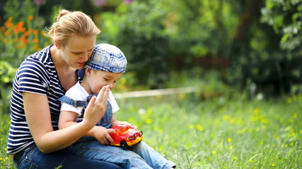 Boy playing with toy car sitting on moms lap outdoor