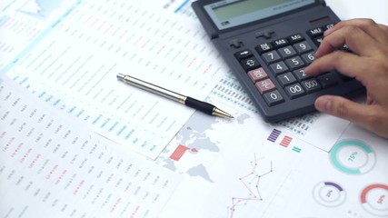 Businessman working with data sheet and using calculator