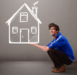 Young boy holding a huge drawn house