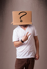 Young man gesturing with a cardboard box on his head with questi