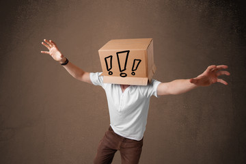 Young man gesturing with a cardboard box on his head with exclam