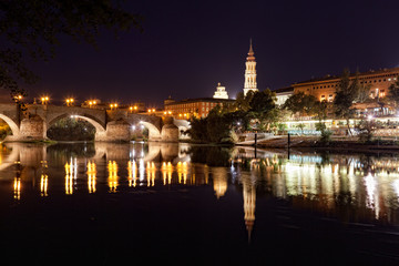 old stone bridge is reflected in river at night, Zaragosa