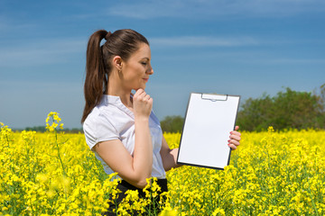 girl with a blank paper file on yellow flower field