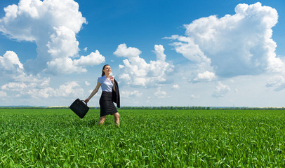 girl with a briefcase walking on the grass