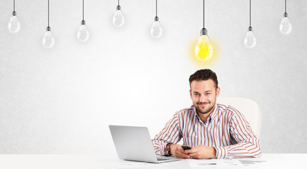 Business man sitting at table with idea light bulbs