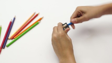 Woman hand using sharpener with color pencil on white desk