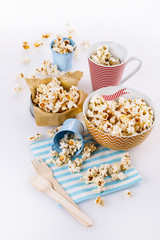 Buttered popcorn in bowls over white background