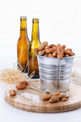 Roasted peanuts on metal bucket over white background