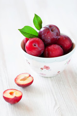 Fresh plums in a bowl, selective focus