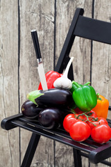 Fresh vegetables on garden chair, selective focus