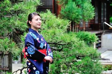 松の木を背景にして立っている着物の女性