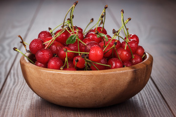 wooden bowl full of cherries on table