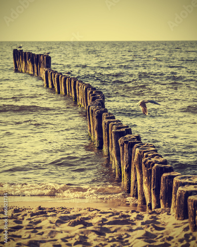 Wood pilings on beach, vintage retro instagram effect. © MaciejBledowski