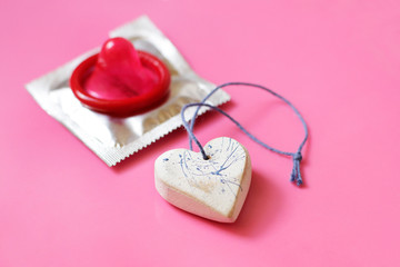 Heart and red condom on pink background