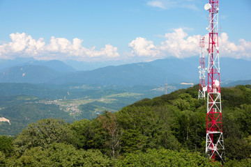 metallic broadcasting tower on the top of high mountain