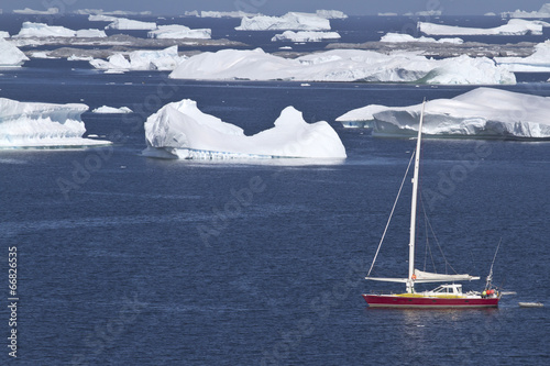 Deurstickers Antarctica sailing yacht in Antarctic waters between beautiful icebergs