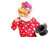 Female clown holding a magician hat