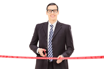 Businessman cutting a red tape