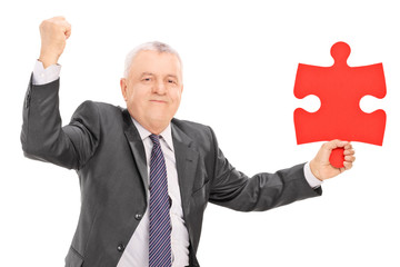 Joyful businessman holding a piece of puzzle