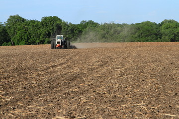 White Tractor Tilling Field