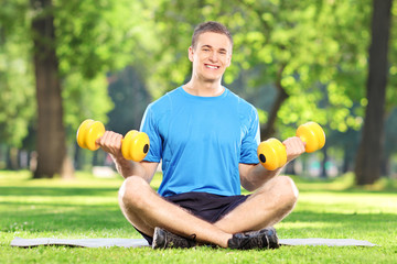 Man exercising with dumbbells in a park