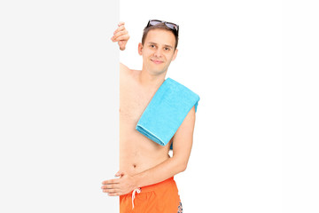 Man in swimsuit standing behind panel