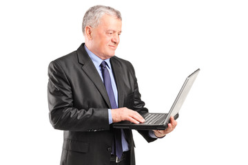 Mature businessman holding a laptop