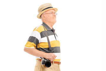 Mature tourist with camera walking