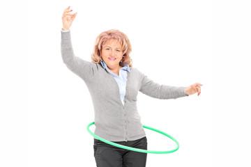Mature woman spinning a hula hoop