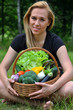 Blond woman sitting holding a basket with vegetables, smiling