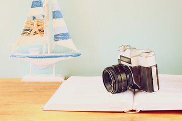 vintage camera, book and decorations over wooden shelf