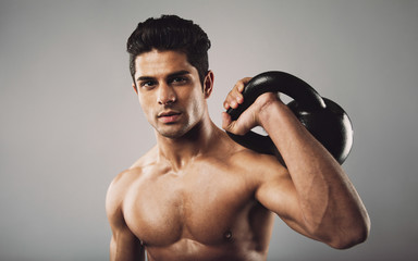 Hispanic fitness male model holding kettle bell