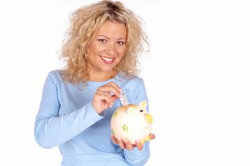 Frau spart Geld im Sparschwein