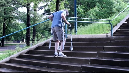 maturer man using a walker to ascend a set of steps