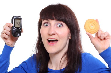 Surprised woman holding glucometer and cake