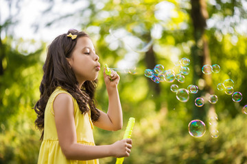 Little girl blowing soap bubble