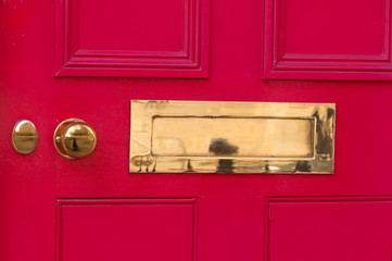 Close-up of a red front door and letter box