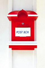 Red wooden mail box on white wall