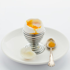 Soft boiled egg in egg cup on white background