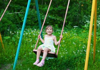 Little beautiful girl swinging in park