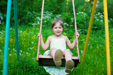 Little beautiful girl swinging in park