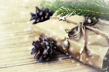 Christmas packed present with x-mas tree branches and pine cones