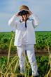 Little boy standing in farmland using binoculars