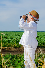 Little boy standing in farmland using binoculars