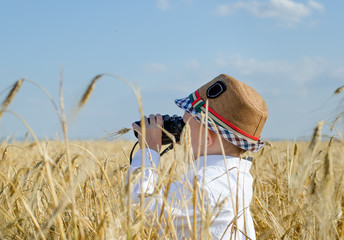 Little boy hiding in a wheat field bird watching