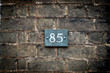 Close up of number 85 on a brick wall
