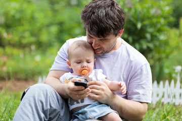 Father holding a baby and texting on his mobile