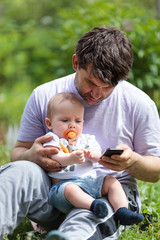 Father using a mobile with a baby on his lap